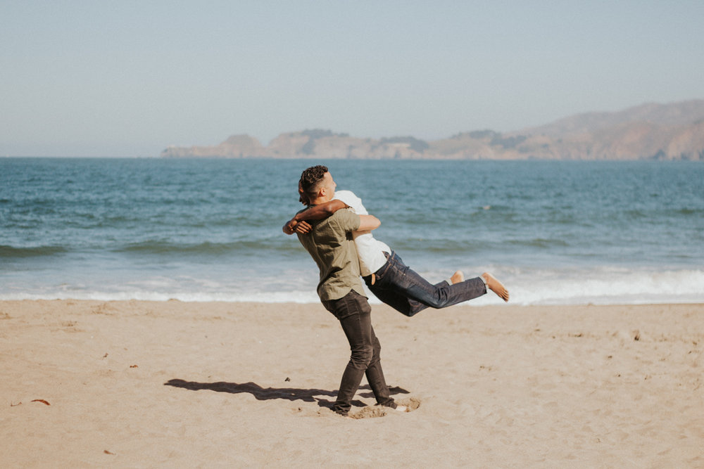 couples session baker beach san francisco california caleb leaping into eugene's arms with ocean and cliffs in background