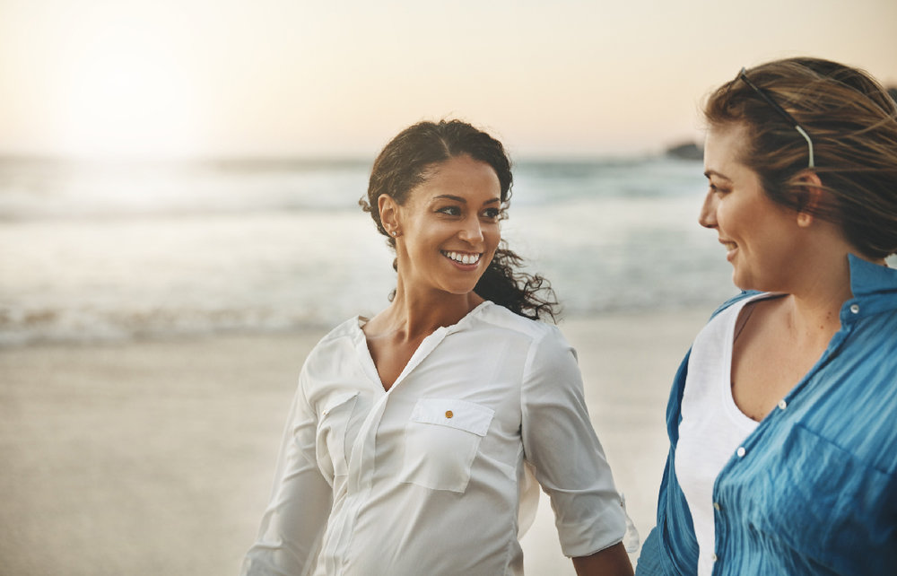 Two women engaged same-sex LGBTQ couple walking on beach holding hands at sunset