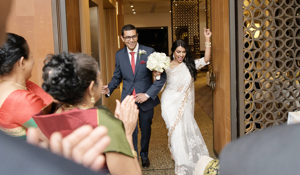 sri lankan wedding in sydney australia newly married couple exiting venue while guests clap
