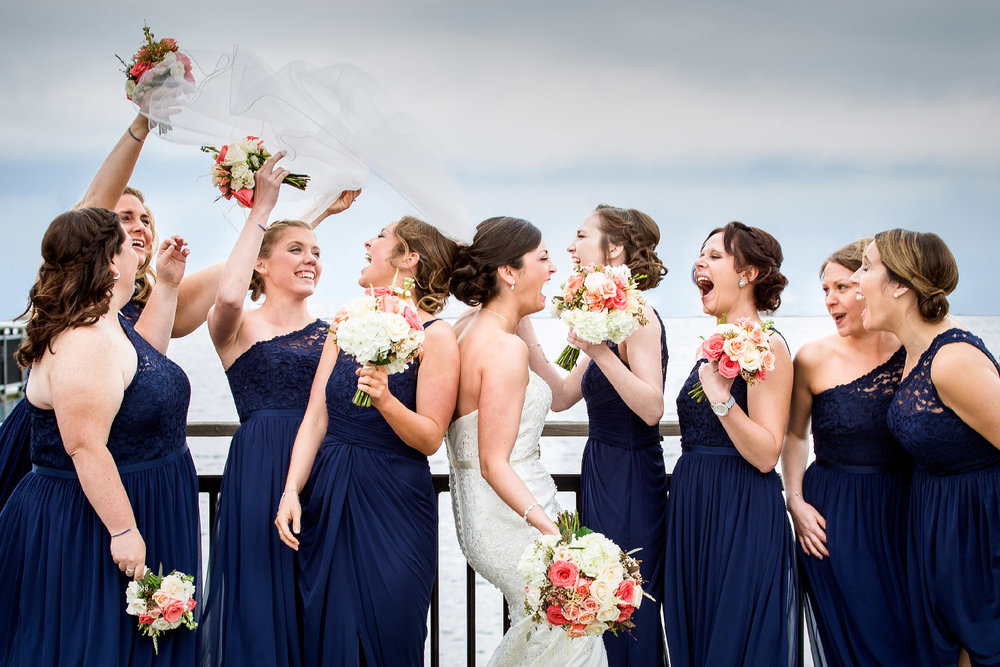 Bride in wedding dress laughing and celebrating with bridesmaids in navy dresses by water Upstate New York Wedding Photographer Jacqueline Connor Photography