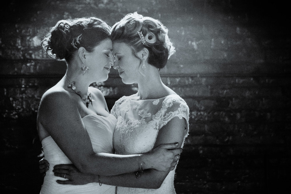 two brides on wedding day hugging and touching foreheads in front of brick wall Buffalo New York Wedding Photographer Jacqueline Connor Photography