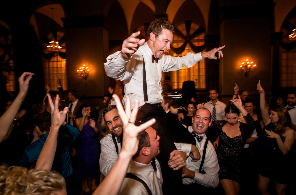 Wedding party and guests celebrating and carrying groom out on shoulders at reception Buffalo New York Wedding Photography Jacqueline Connor Photography