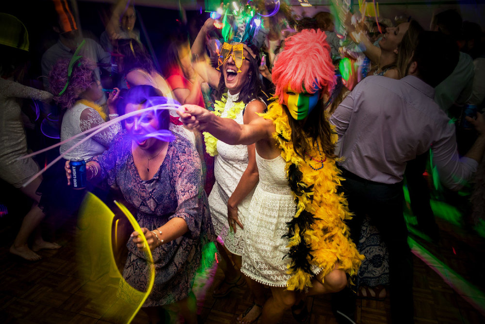 Wedding guests celebrating and dancing at reception with feather boas glow sticks and masks Upstate New York Wedding photographer Jacqueline Connor Photography