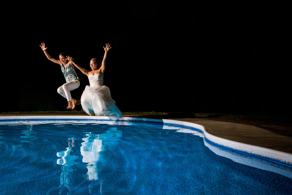 Two brides dressed in wedding dress and white pants and blue blouse jumping into swimming pool at reception Buffalo New York Wedding Photographer Jacqueline Connor Photography