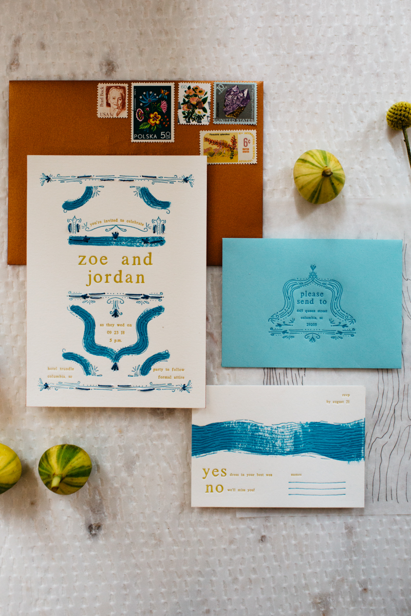 wes anderson inspired wedding styled shoot columbia south carolina invitations and rsvp envelopes, small gourds scattered on table