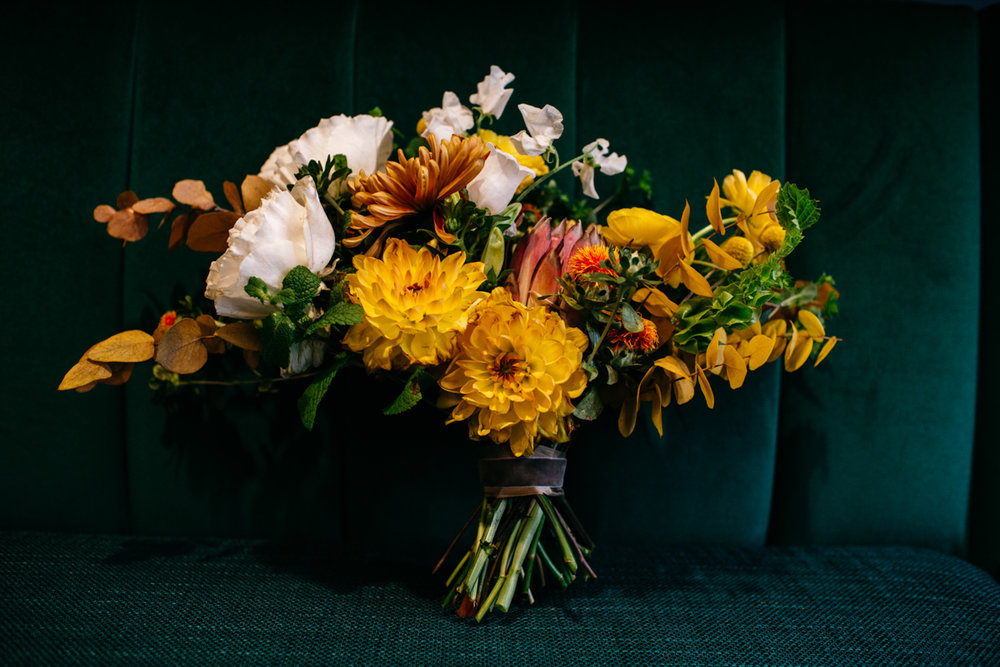 wes anderson inspired wedding styled shoot columbia south carolina colorful bouquet resting on plush seat