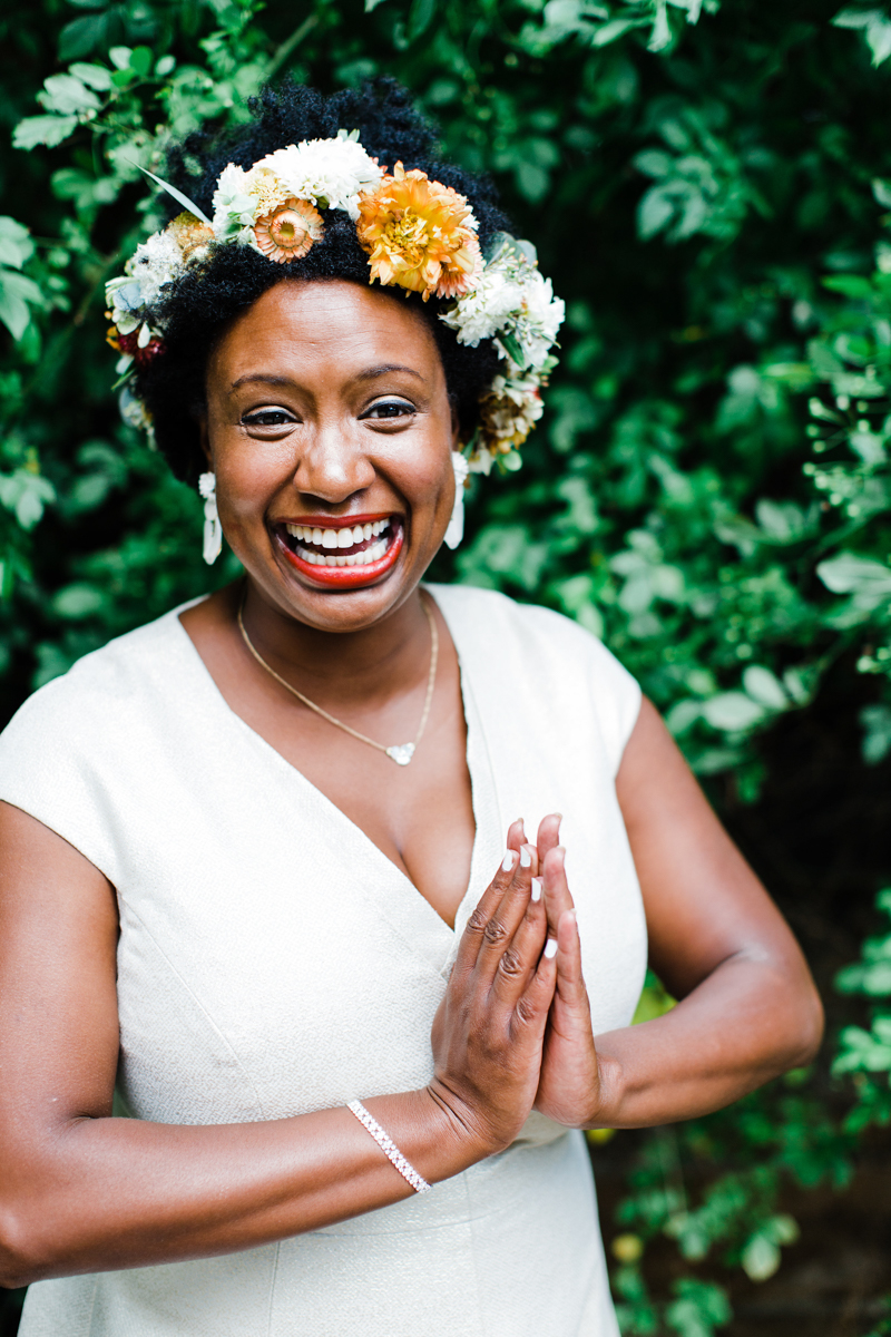 Bride smiling and clapping her hands together in modern v-neck gown and orange and white flower crown