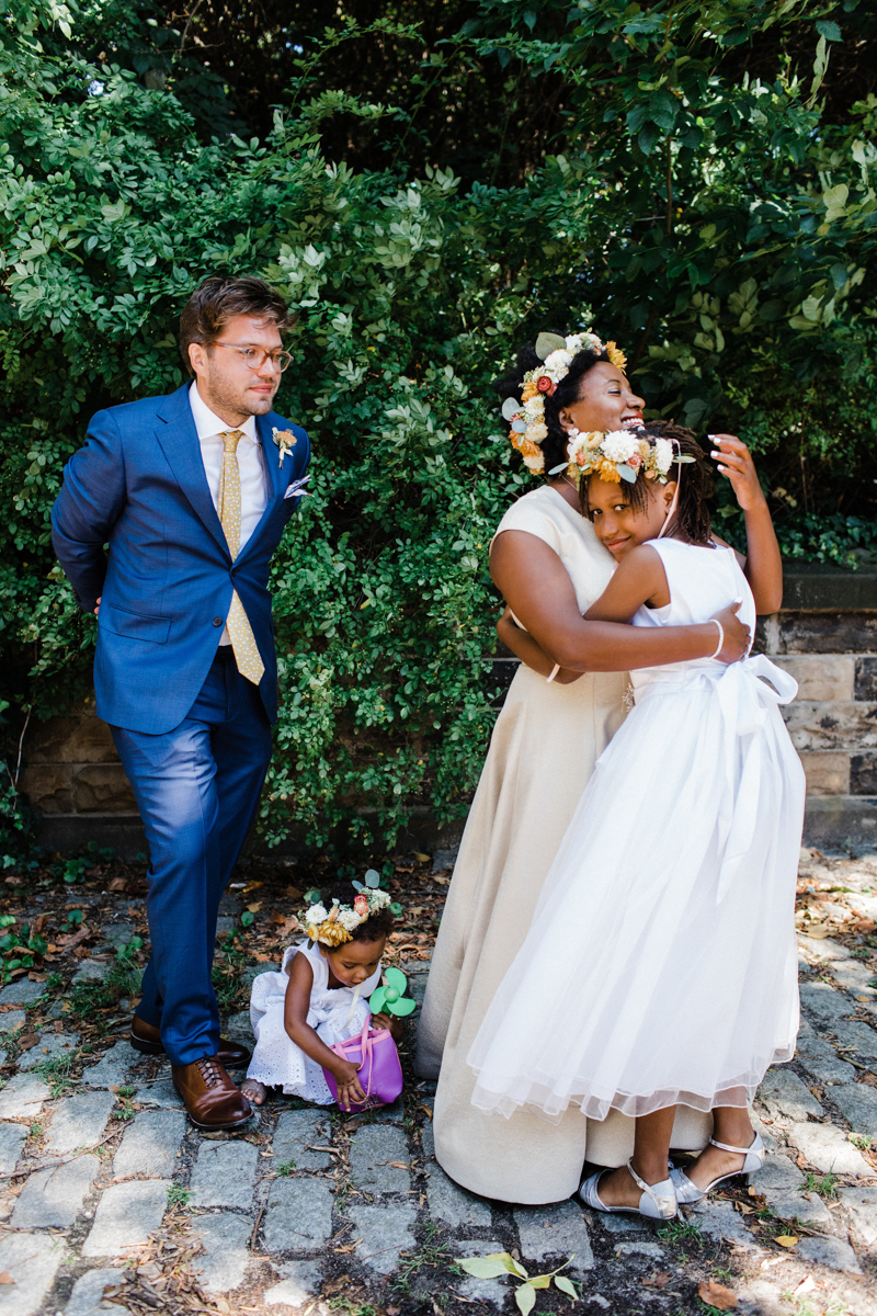 Flower girl hugging bride before wedding in Brooklyn