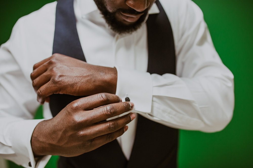 Travis putting on cufflinks and getting ready before wedding while standing against bright green wall in Charlotte North Carolina