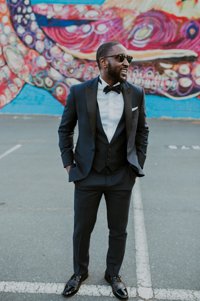 Groom smiling in his black suit and bow tie and sunglasses in parking lot in front of bright colorful mural