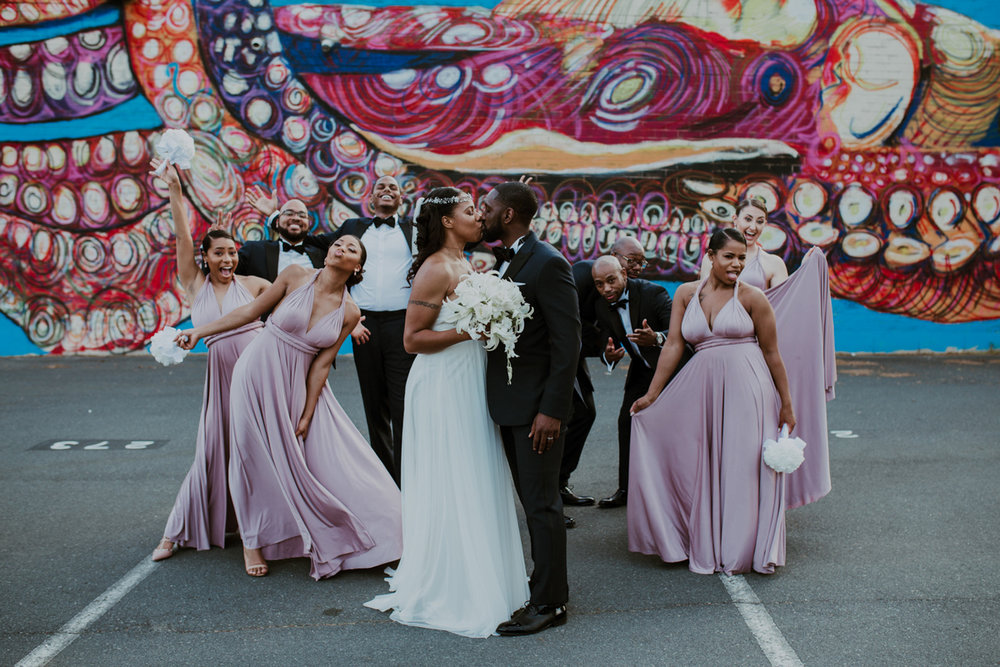 Travis and Shavonne kiss with bridesmaids and groomsmen making faces behind them in parking lot in front of colorful mural