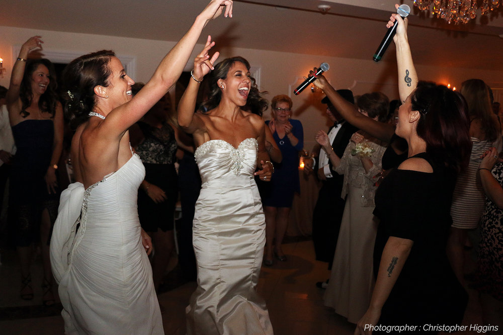 two brides jumping up and down on dance floor and singing along to live music The Metropolitan Players NYC