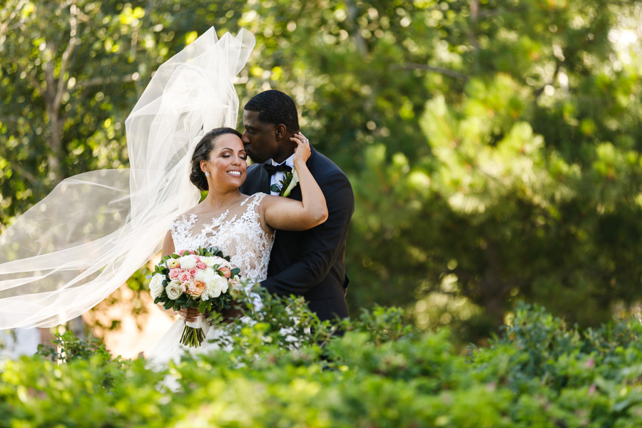 african american, christian, and muslim traditions minneapolis wedding glenn kissing taara's forehead in garden