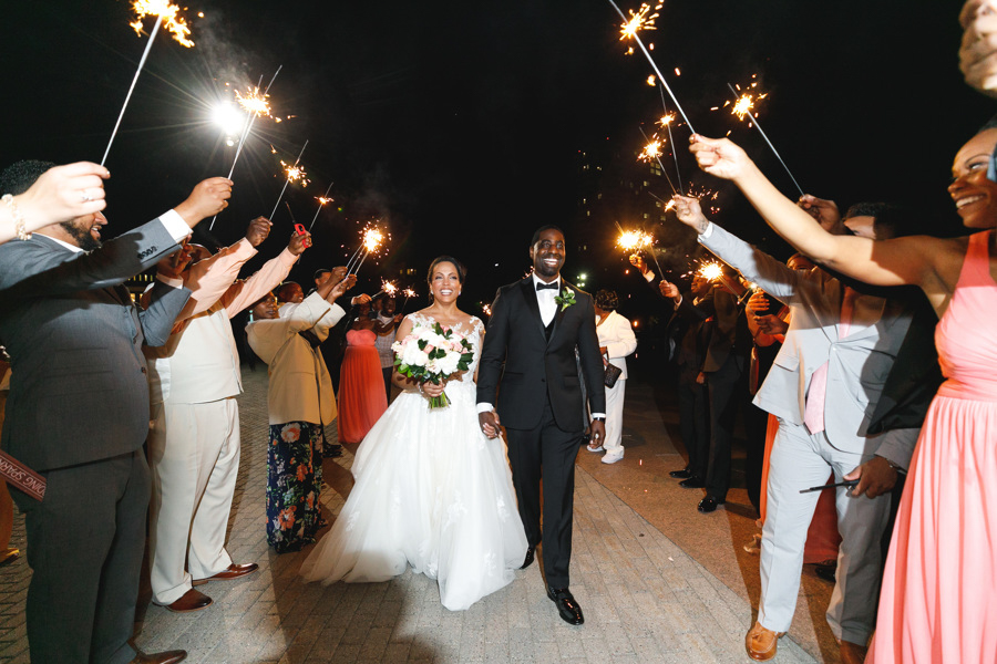 african american, christian, and muslim traditions minneapolis wedding couple leaving while guests hold sparklers along path