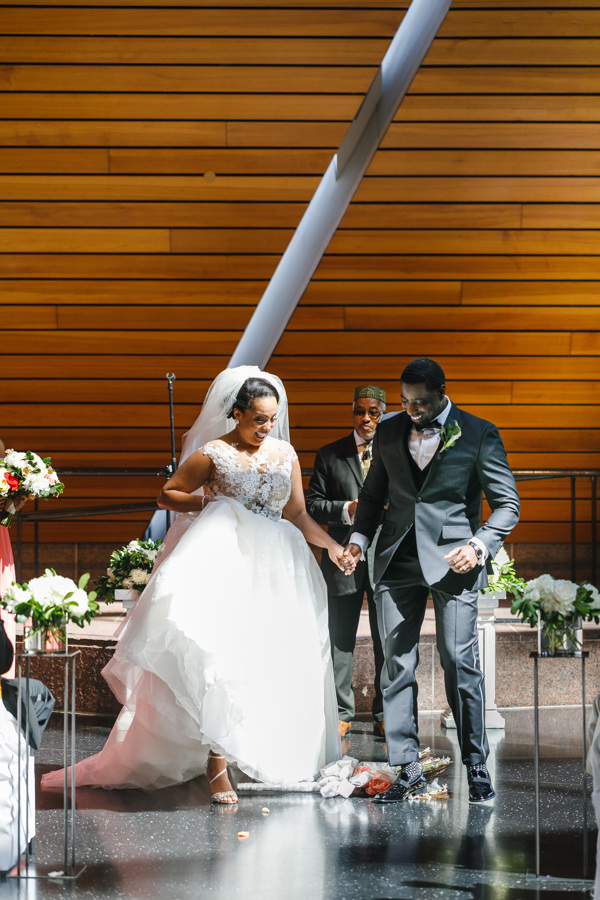 african american, christian, and muslim traditions minneapolis wedding couple jumping broom during ceremony