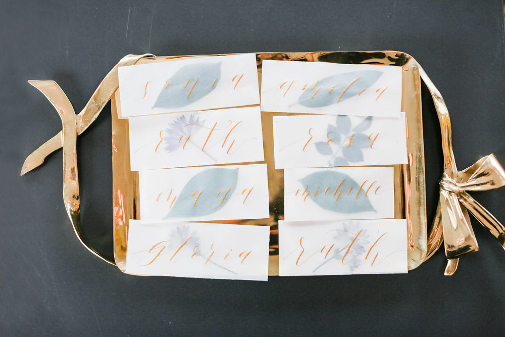 Modern traditional blended styled shoot new york name cards with guests' names in gold script resting on gold tray
