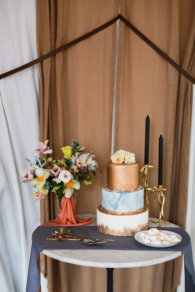 Modern traditional blended styled shoot new york cake table with candlesticks, vase of flowers, and utensils