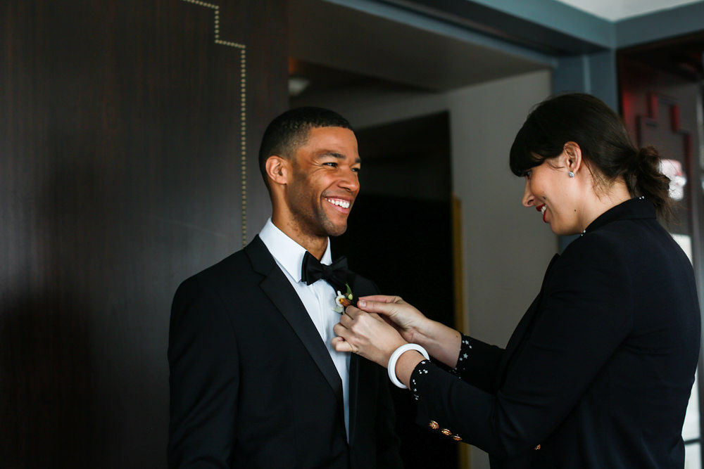 Modern traditional blended styled shoot new york groom having boutonniere put on lapel