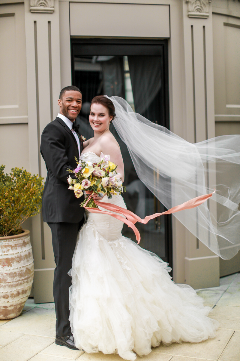 Modern traditional blended styled shoot new york couple outside nomad hotel, breeze blowing veil and bouquet's ribbon