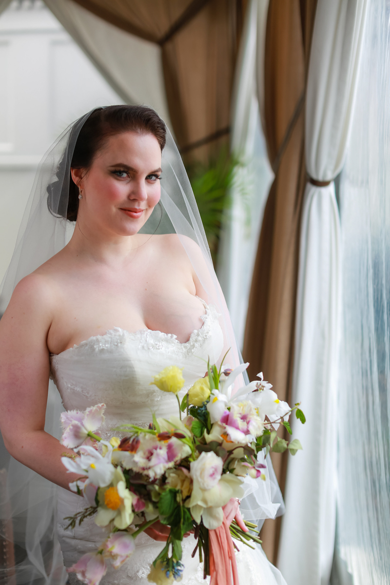 Modern traditional blended styled shoot new york bride at window holding bouquet