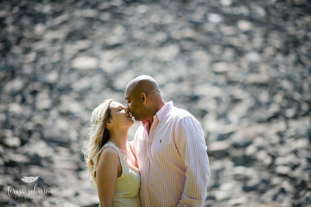wedding engagement photos of couple about to kiss in front of water and stone connecticut photographer Teresa Johnson