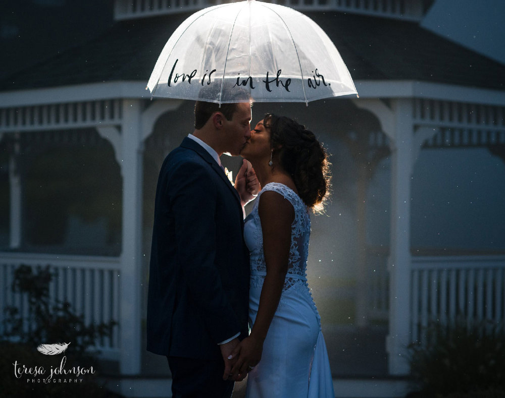 newlywed couple standing under umbrella that reads love is in the air connecticut wedding photographer teresa johnson