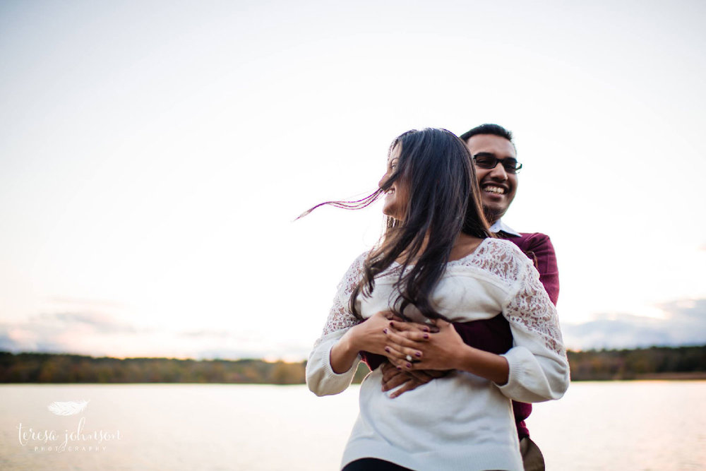 couple hugging by lake for engagement photos by connecticut wedding photographer teresa johnson