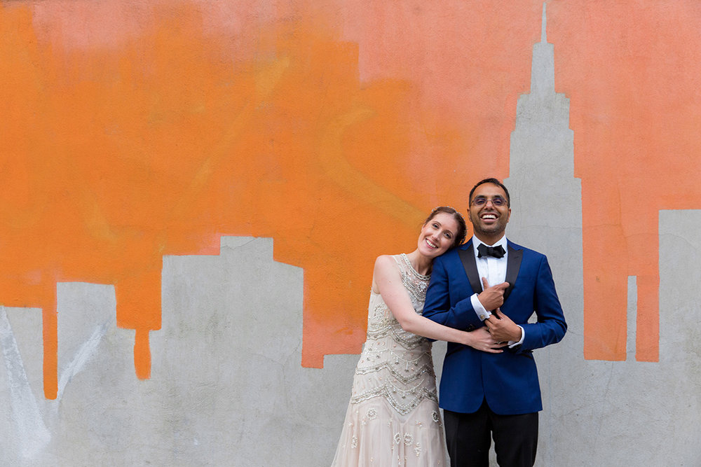 newlywed couple embraced and smiling in front of mural wall Justin McCallum Photography New York City
