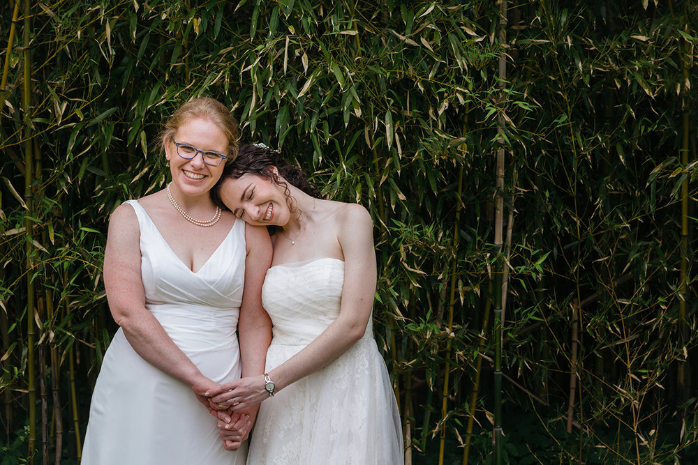 two brides snuggling and holding hands in from of bamboo Justin McCallum Photography New York City