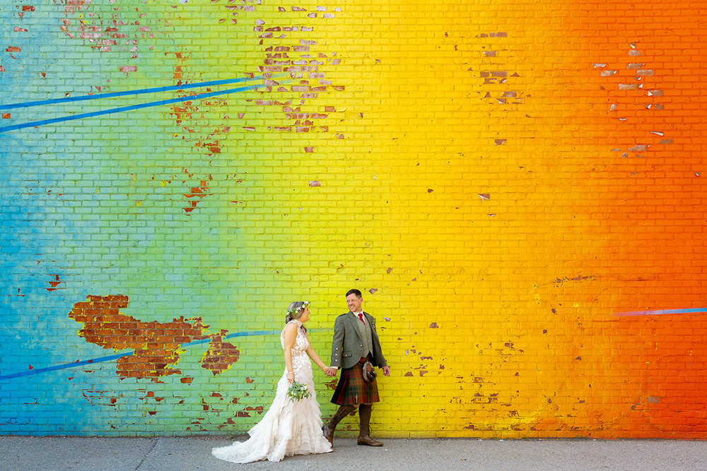 bride and groom wearing kilt walking and holding hands in front of rainbow gradient mural wall Justin McCallum Photography New York City