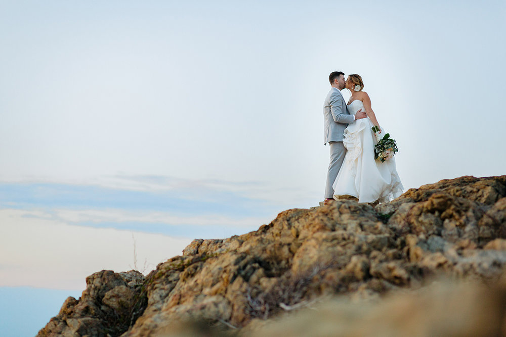 bride and groom kissing on rocky cliff by the ocean by Justin McCallum NYC wedding photographer