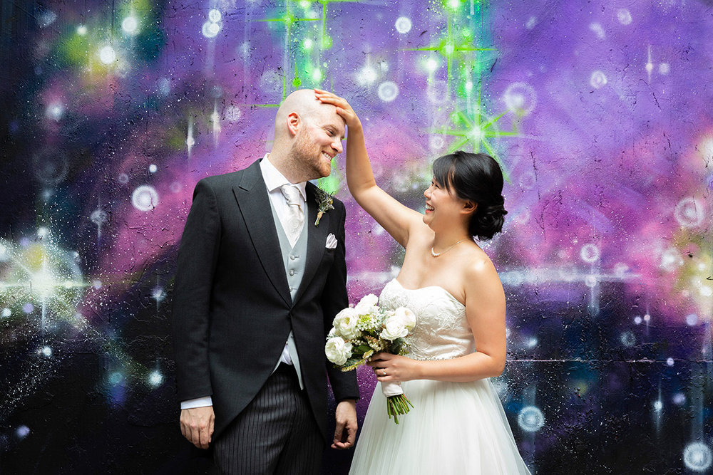 bride touching grooms head in front of galaxy mural wall by NYC wedding photographer Justin McCallum
