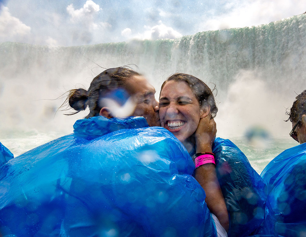 couple kissing and smiling in blue parkas at Niagra Falls by NYC wedding photographer Justin McCallum