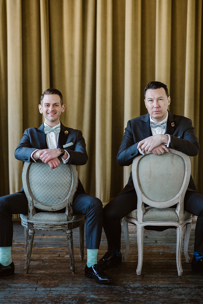 two grooms smiling and straddling backwards chairs by nyc wedding photographer Justin McCallum