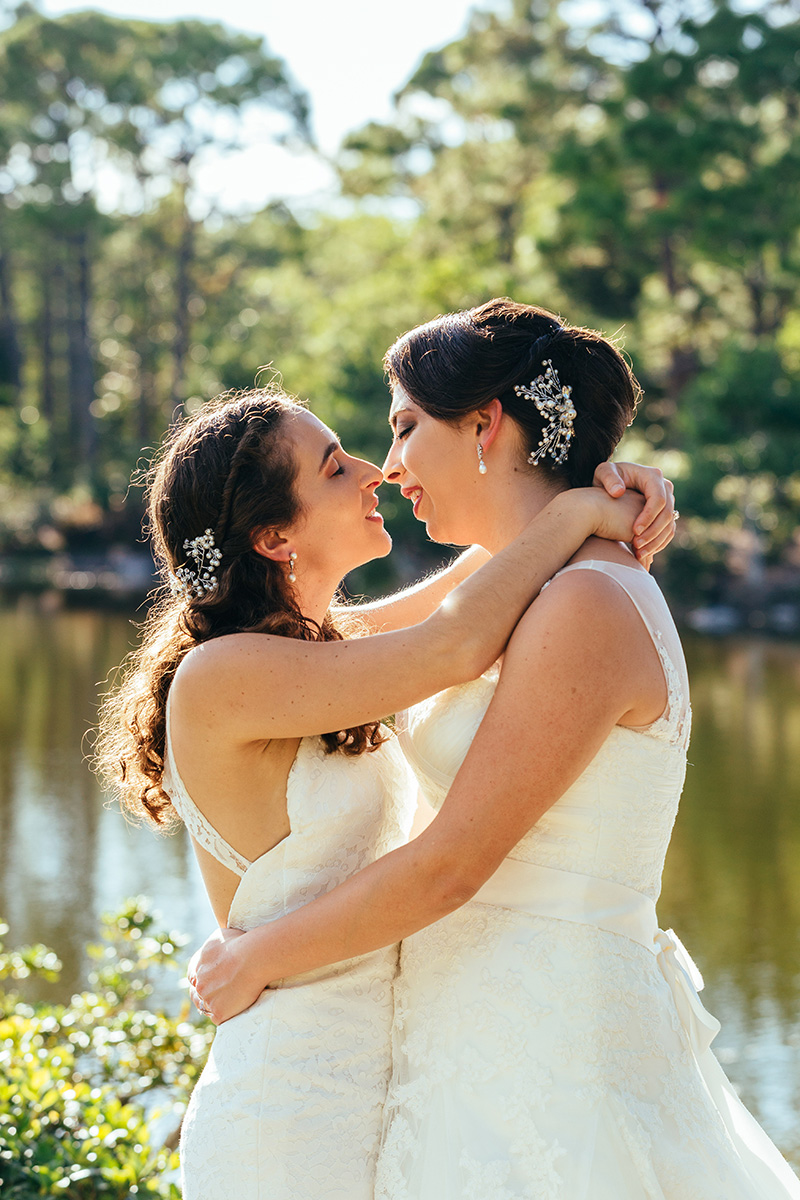 two brides embraced and about to kiss in front of lake in the woods by nyc wedding photographer Justin McCallum
