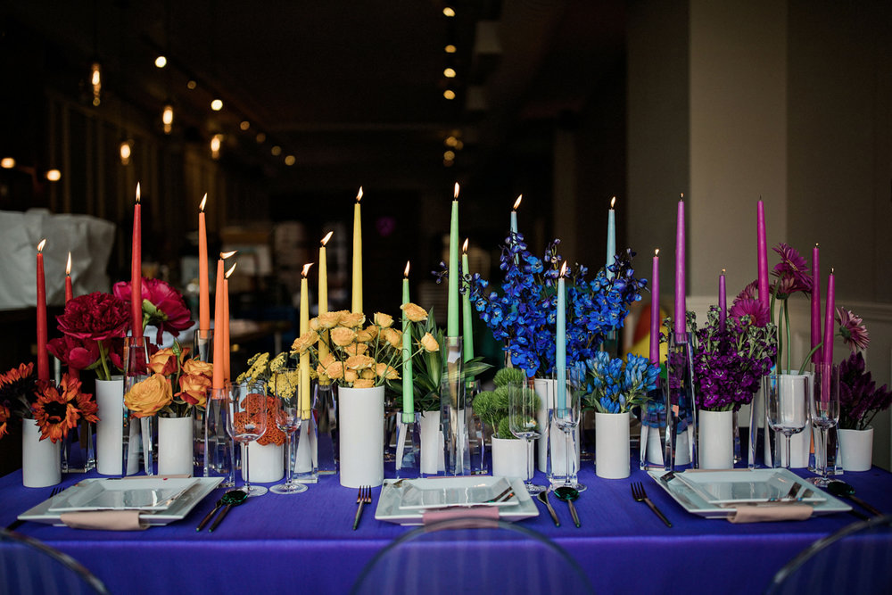 80s themed pride party brooklyn new york set table with rainbow spectrum of taper candles and vases of flowers