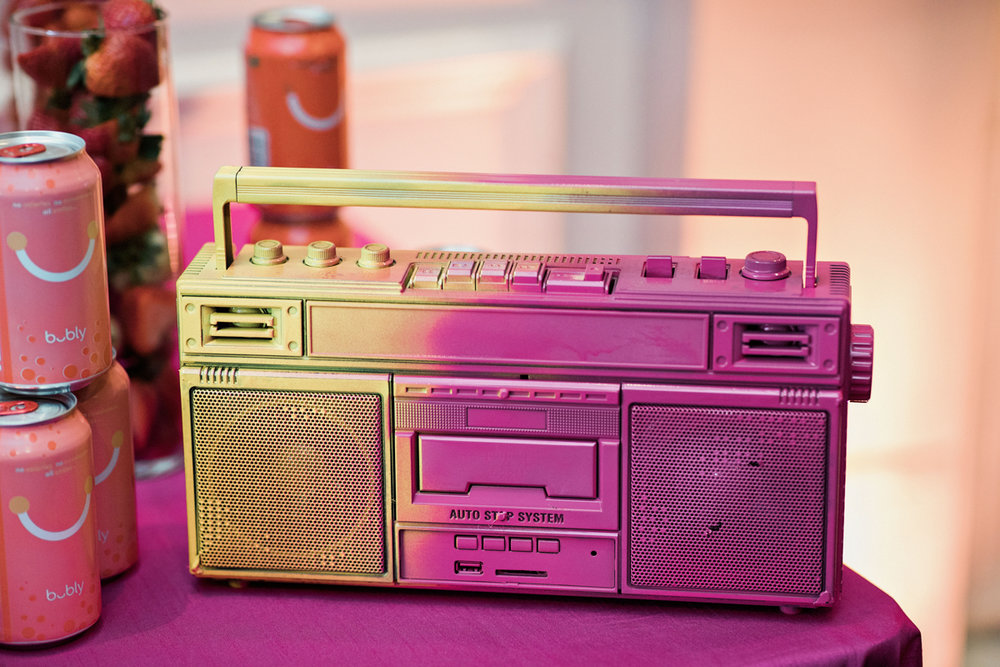 80s themed pride party brooklyn new york iridescent boombox on table with Bubly drinks and tall vase of strawberries