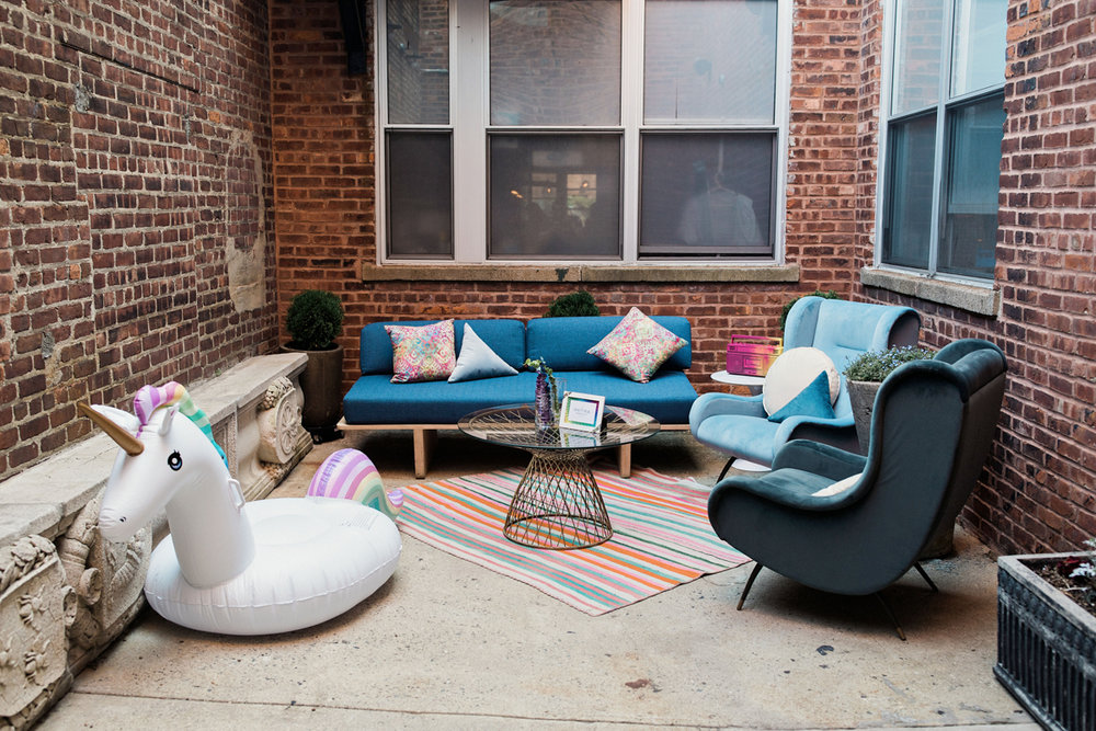 80s themed pride party brooklyn new york outside area with chairs, sofa, and inflatable unicorn float