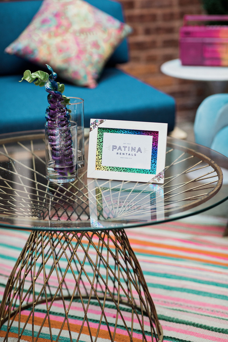 """80s themed pride party brooklyn new york table in outside courtyard with card reading """"patina rentals"""""""