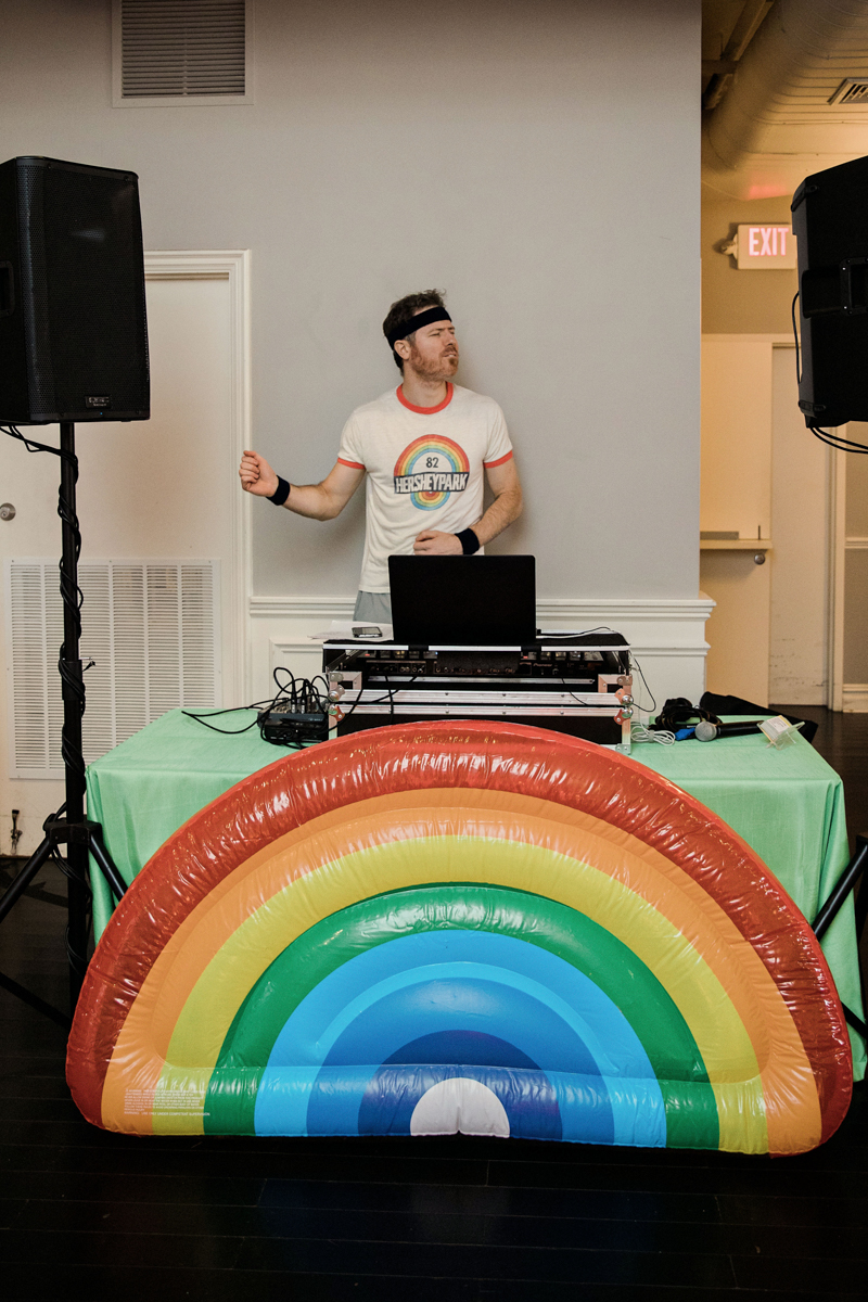 80s themed pride party brooklyn new york dj rob kelley at table with inflatable rainbow in front