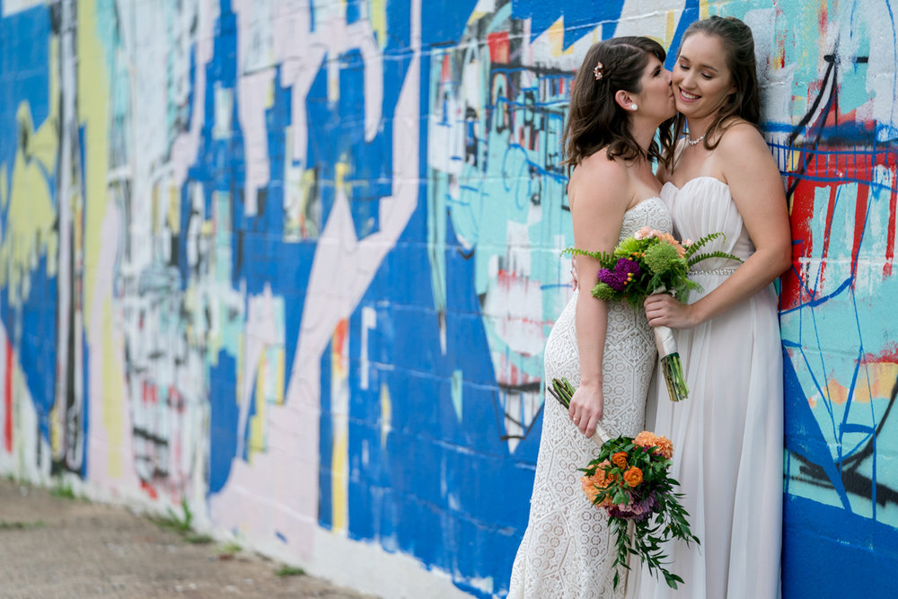 Brewery wedding washington D.C. kiss on cheek in front of wall mural