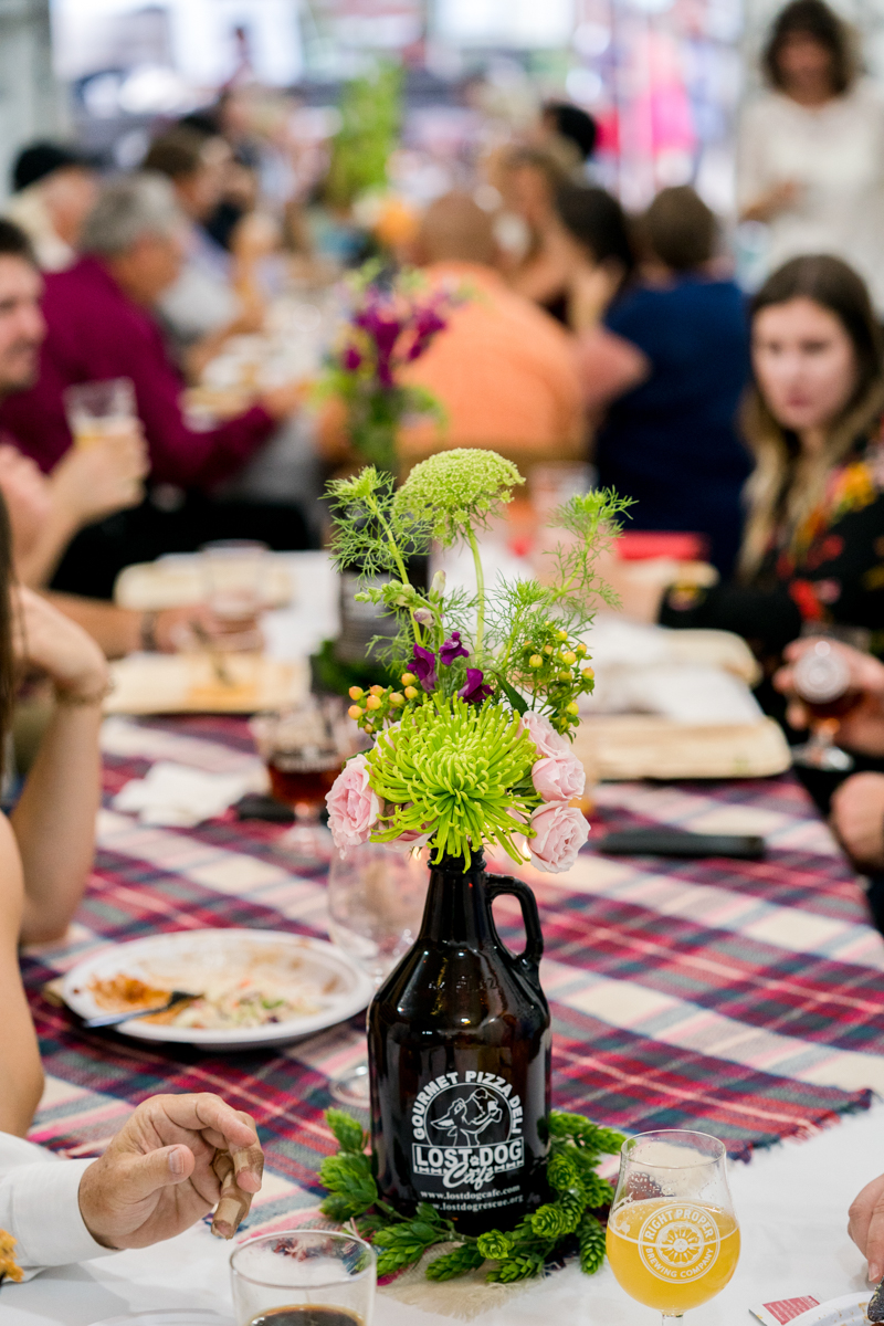 Brewery wedding washington D.C. guests at long tables with floral centerpieces in beer growler