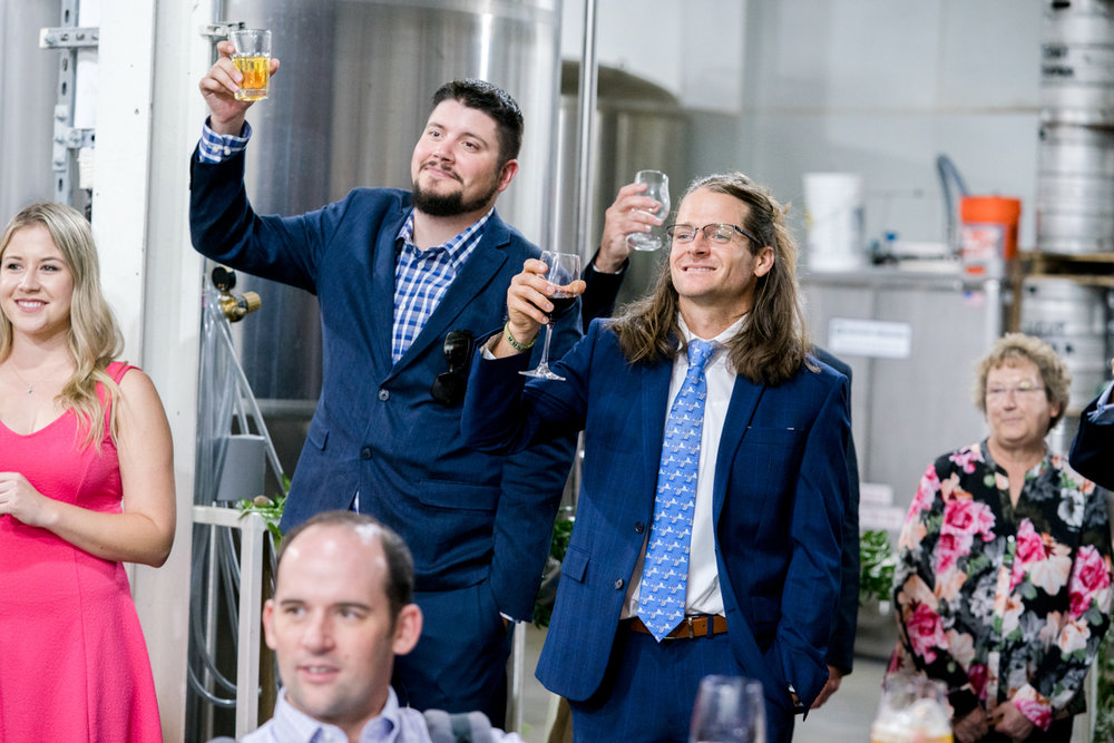 Brewery wedding washington D.C. guests lifting glasses in toast