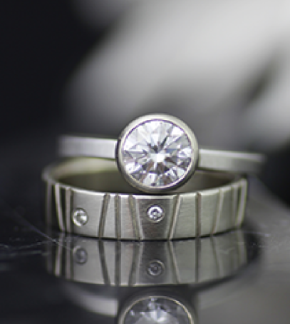 Asymmetrical textured wedding band and solitaire engagement ring