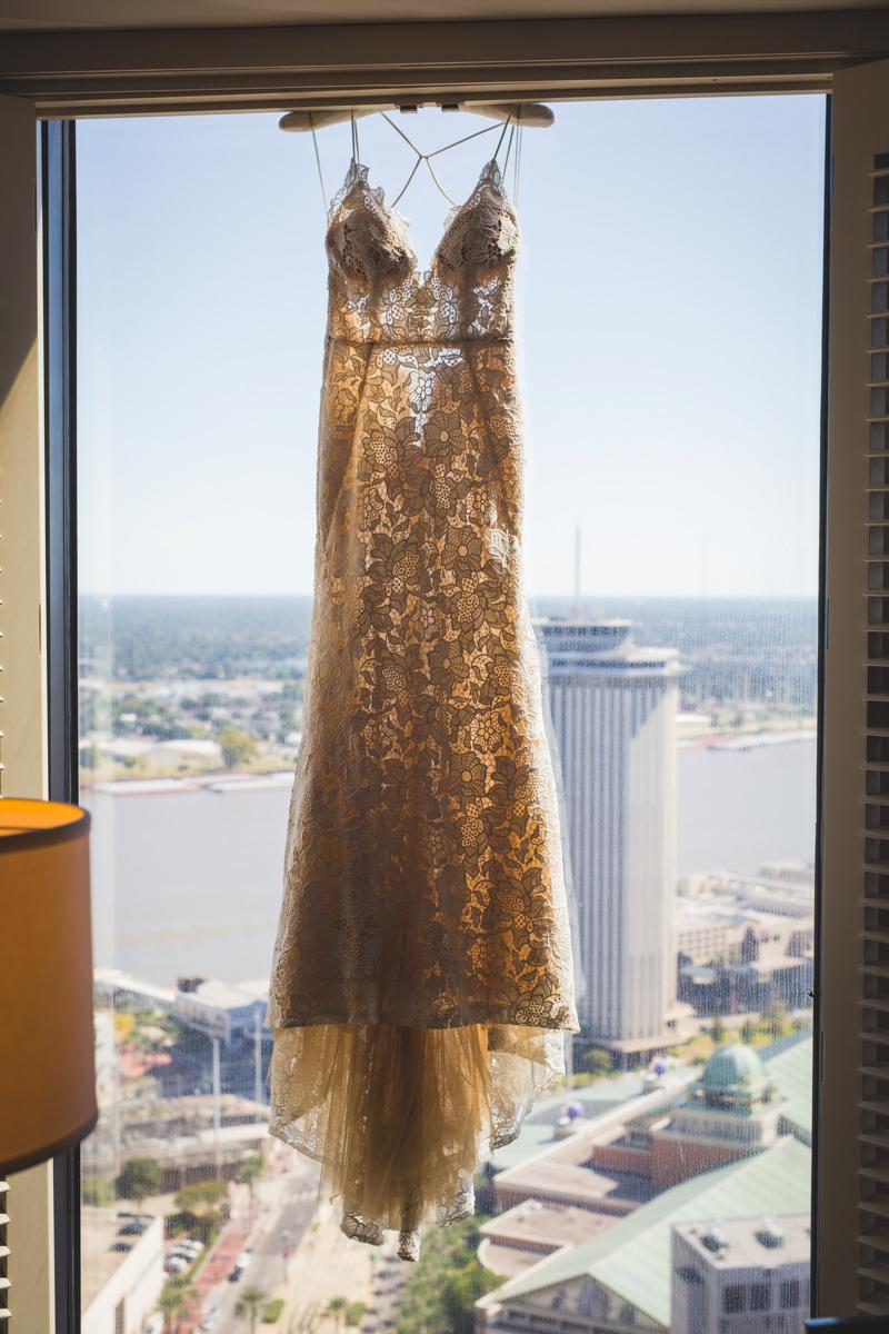 New Orleans Destination Wedding dress hanging at window overlooking river