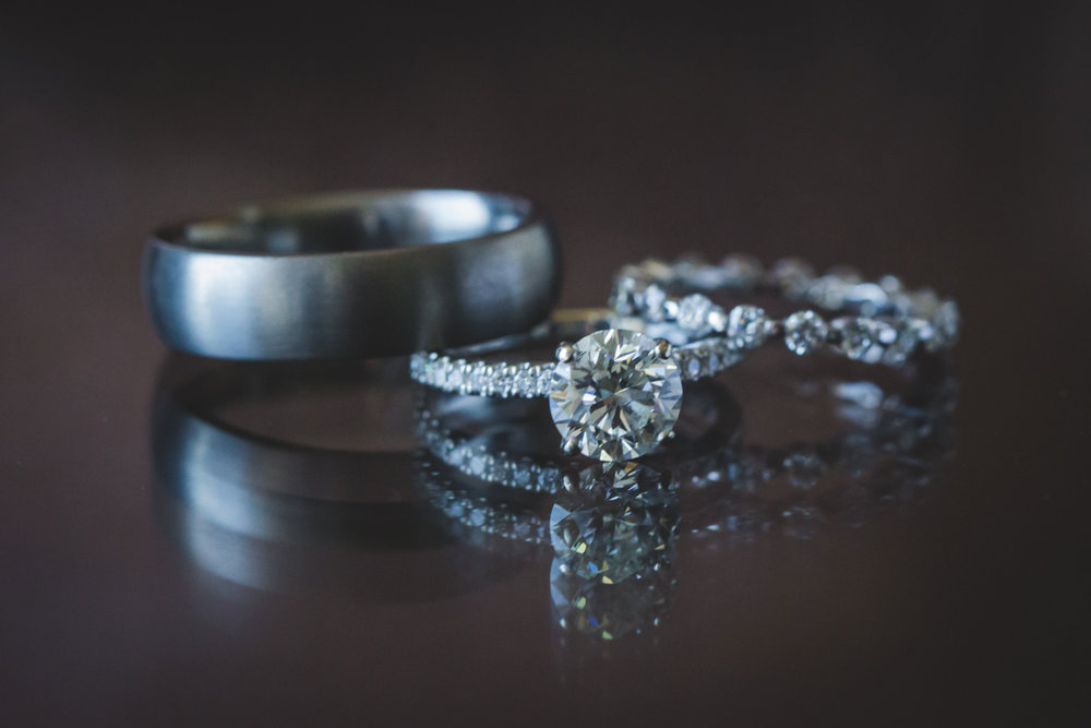 New Orleans Destination Wedding wedding rings on glossy table