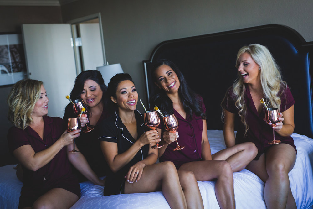 New Orleans Destination Wedding bride and bridesmaids on bed drinking wine