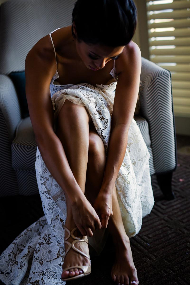 New Orleans Destination Wedding jessica in wedding dress fastening shoe