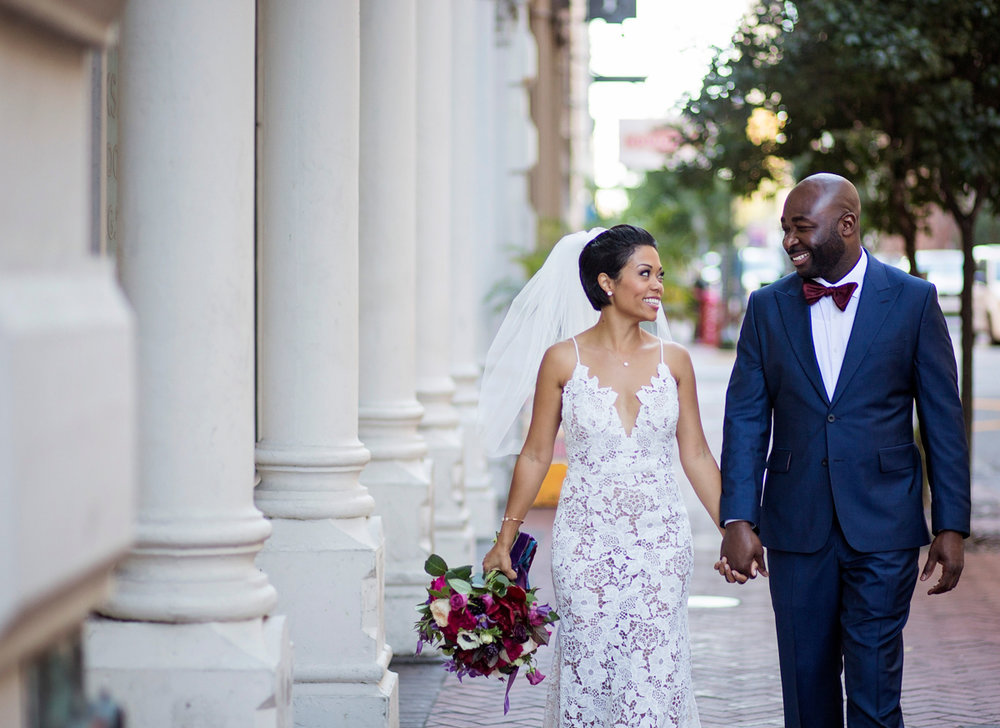 New Orleans Destination Wedding darius and jessica walking down brick path holding hands