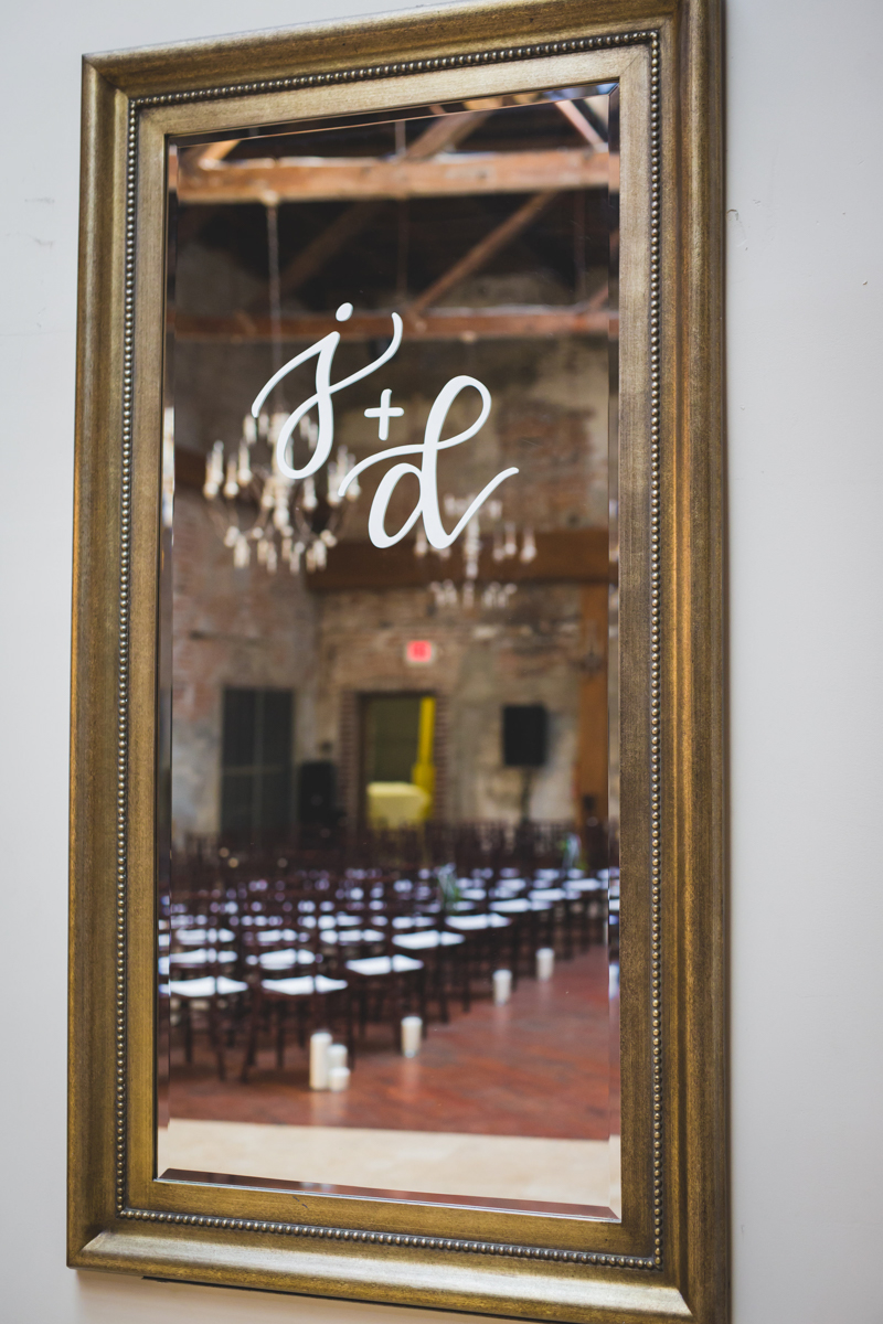 """New Orleans Destination Wedding mirror with """"j + d"""" painted on it reflecting back venue"""